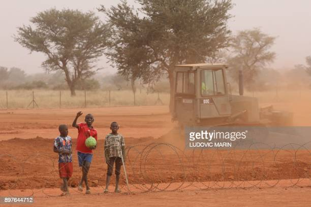Nigerien children walk and play along the fences of the Barkhane French air force base on December 23 in Niamey / AFP PHOTO / ludovic MARIN