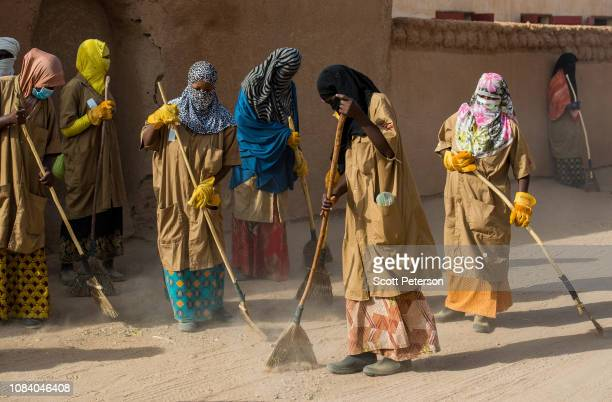 Nigerien men and women sweep the streets in a program run by the German aid agency GIZ, part of an EU stabilization project to provide jobs, on...