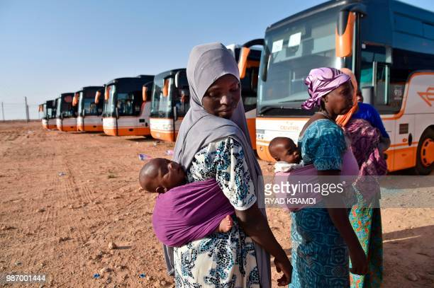 Nigerien migrants in Algeria wait next to buses as they are repatriated by Algerian authorities back to Niger on June 29 in Laghouat northern Algeria