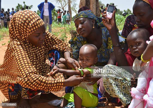 TOPSHOT Nigerien mothers use a MUAC measuring tape as part of local malnutrition education on July 14 2016 in the southern village of Barago Niger is...