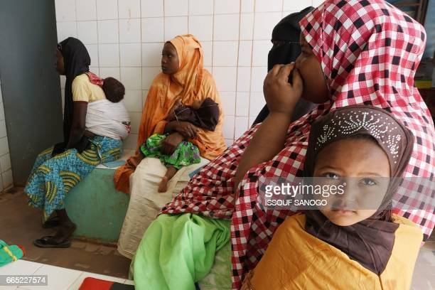 Nigerien mothers wait with their babies to receive treatment at the Prince Albert of Monaco dispensary in Agadez on April 6 2017 / AFP PHOTO / ISSOUF...