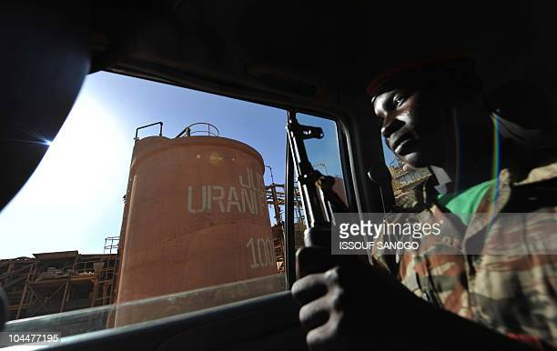 Nigerien soldier sits inside a car escorting press members outside France's stateowned nuclear giant Areva's uranium mine on September 26 2010 in...