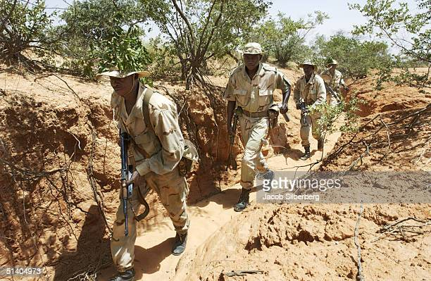 Nigerien soldiers run through a ravine in order to sneak up on a target during a training exercise September 22 2004 in Samara Niger Through the...
