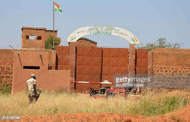 A Nigerien soldiers walks near calcined motorcycles used by assailants in front of the the prison of Koutoukale near Niamey following an attack on...