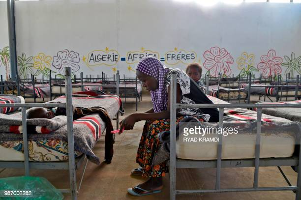 A Nigerien woman waits with children in a transit camp as Nigerien migrants in Algeria are repatriated by Algerian authorities back to Niger on June...