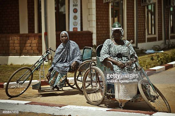 Nigerien women are seen on makeshift wheelchairs during the opening ceremony of Lamorna Hospital's eye unit in the Abdou Moumouni university with the...