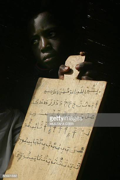 A Nigerois boy holds his notes during a lesson iat the