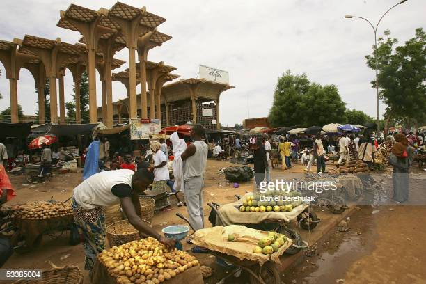 Nigerois man rearranges his produce at the central Niamey market place on August 12 2005 Niamey Nigeria Niamey is the Capital of Niger Niger is...
