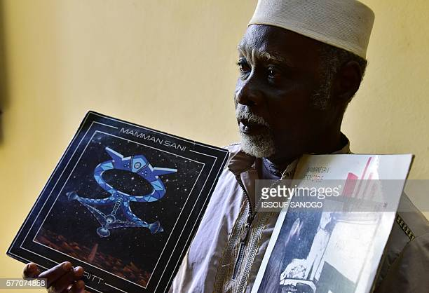 Niger's selftaught legendary musician Mamman Sani poses with his first and second albums on June 21 2016 in Niamey SANOGO