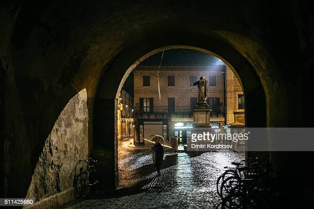 Night city scene in Old Town of Ferrara with statue of Girolamo Savonarola on a background