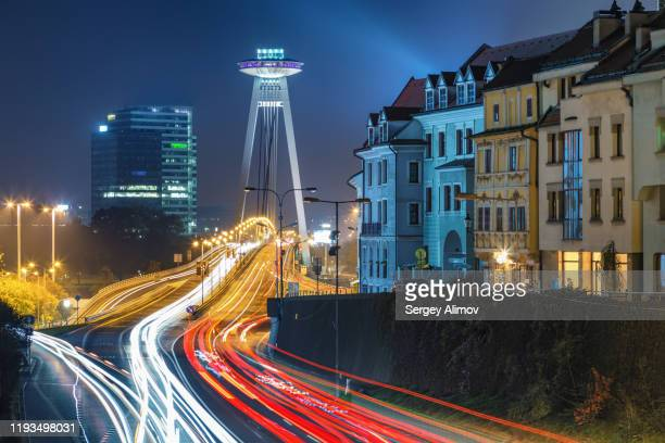 night cityscape of bratislava downtown and illuminated ufo tower - slovakia stock pictures, royalty-free photos & images