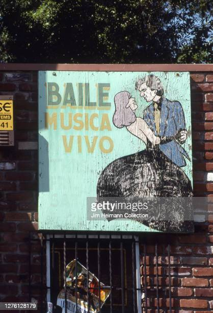Night club in the Lincoln Heights neighborhood of Los Angeles, California has a deteriorating wooden sign showing two people dancing on its brick...