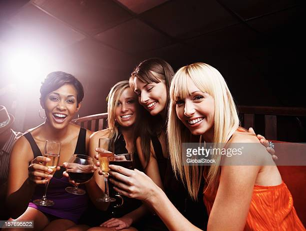 Night club - Smiling young female friends enjoying drinks