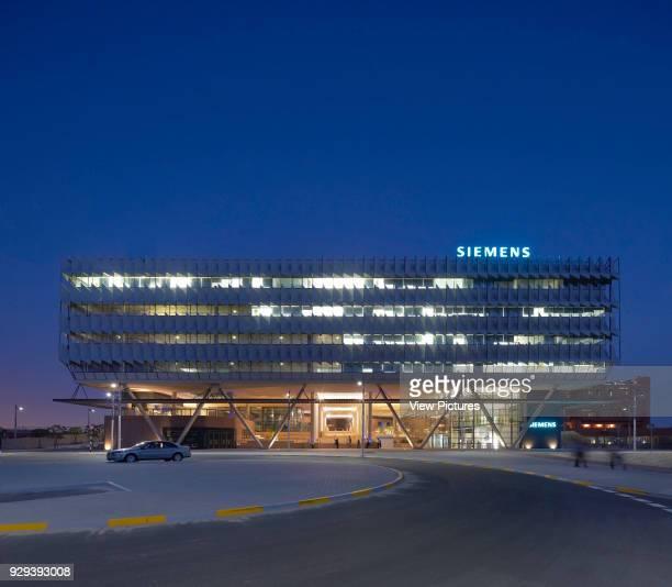 Night elevation from approach. Siemens Masdar, Abu Dhabi, United Arab Emirates. Architect: Sheppard Robson, 2014.