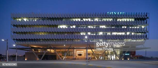 Night elevation with lit interiors. Siemens Masdar, Abu Dhabi, United Arab Emirates. Architect: Sheppard Robson, 2014.