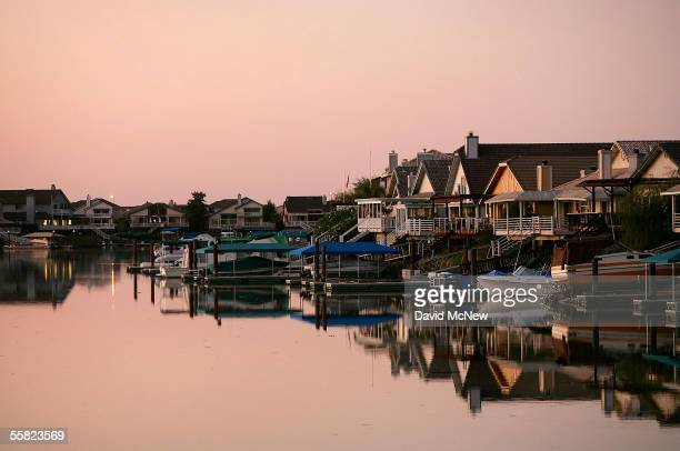 Night falls on a new development of large tract homes with docks and boats in the community of Discovery Bay, one of the residential islands...