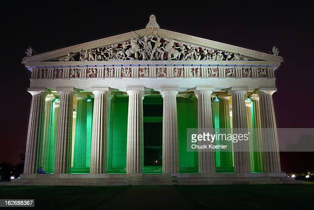 Night image of the Parthenon building in Nashville, TN. A couple sit under one of the columns adding additional point of interest to the colorful...