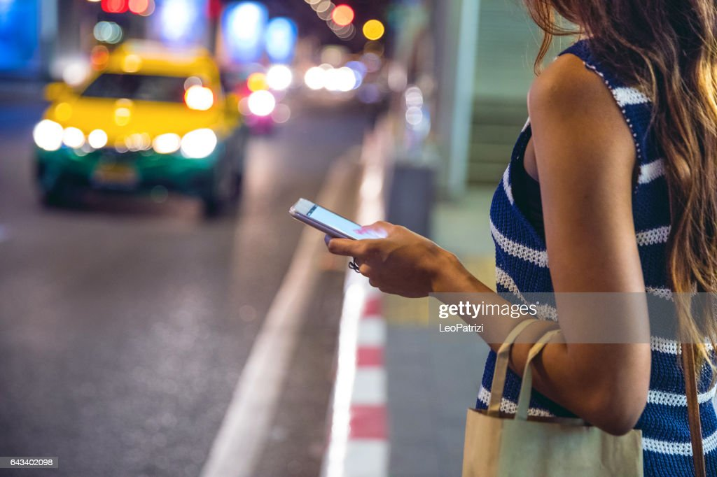 Noite em Bangkok - mulher à espera de um táxi : Foto de stock