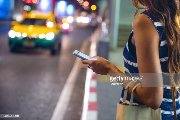 night in bangkok - woman waiting for a taxi - car pooling stock photos and pictures