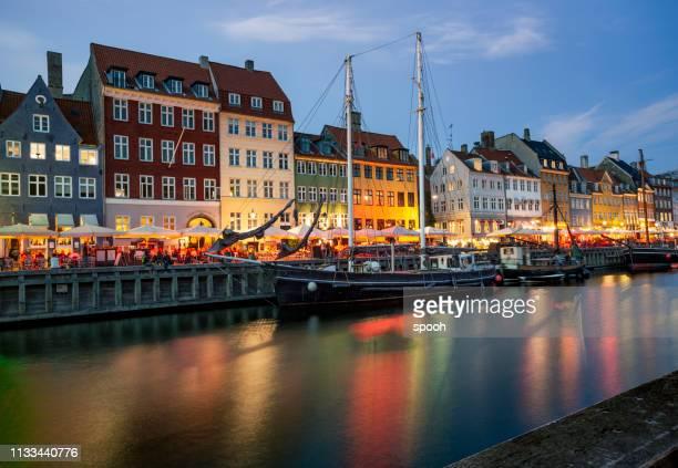 night life in nyhavn waterfront in copenhagen, denmark. - copenhagen stock pictures, royalty-free photos & images