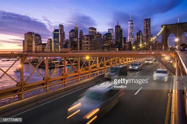 night lights of car headlamps on the brooklyn bridge. brooklyn bridge manhattan new york famous bridge and iconic landmark american travel lifestyle concept - brooklyn new york stock pictures, royalty-free photos & images
