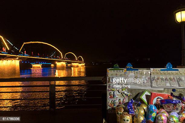 Night market selling North Korea souvenir goods beside the Yalu river. Dandong is the largest Chinese frontier city, bordering with Sinuiju of North...