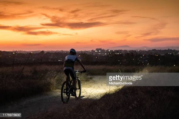 night mtb rider with a light at sunset - california stock pictures, royalty-free photos & images