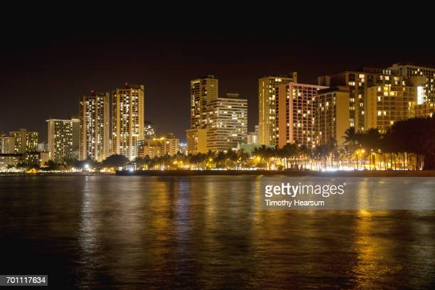 night photo of lighted buildings and their reflections in water - timothy hearsum foto e immagini stock