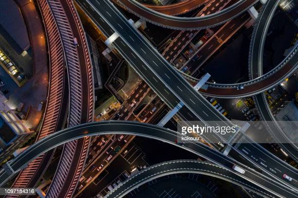 night photograph of complicated intersecting highway. - overhead view of traffic on city street tokyo japan stock photos and pictures