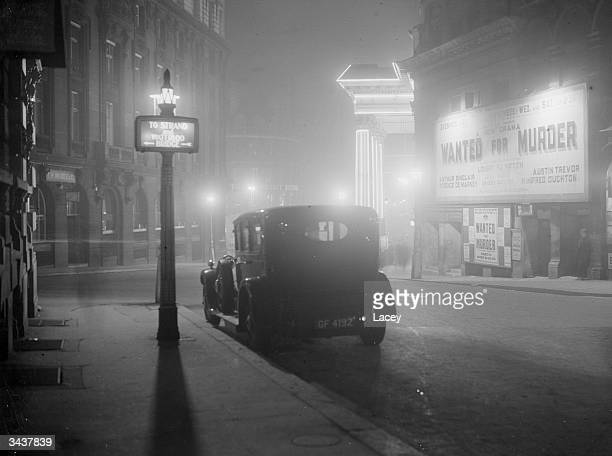 A night scene in central London with an advertisement for the play 'Wanted for Murder'