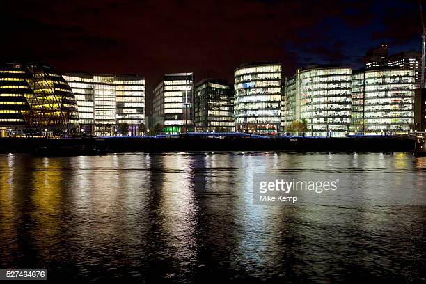 Night scene looking over the River Thames towards the skyline of More London area offices and business district is reflected in the water surface...