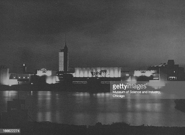 A night scene on the water front shows the illuminated buildings of the Chicago World's Fair at the Century of Progress International Exposition The...