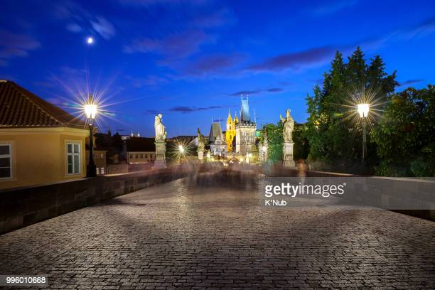 Night scene view of St. NIcholas church and Lesser Town Bridge tower and castle, view from Charles bridge, where is the famous landmark for travel by tourist in Prague or Praha, Czech Republic, Europe