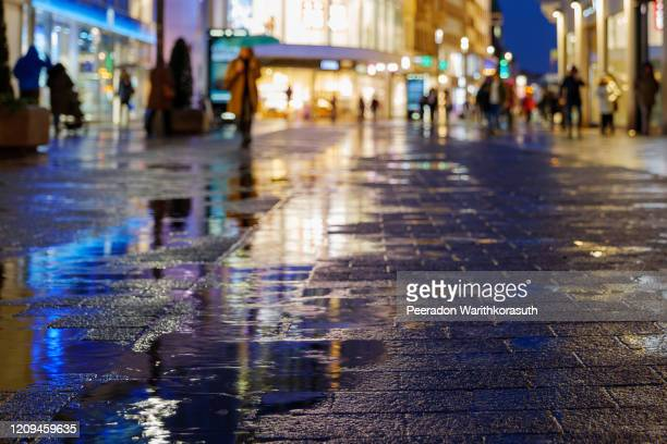 night scenery low angle view of puddle or swamp on walking street or sidewalk in shopping street with blur background of walking people and display of retail shops in düsseldorf, germany after rain. - low angle view photos et images de collection