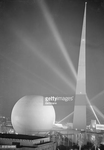 Night shades and the beams of giant searchlights make a black and white background for this view of the Trylon and Perisphere at the New York World's...
