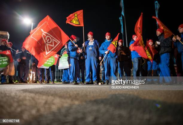 Night shift metal workers of the Kirchhoff Automotive company hold flags with the logo of Germany's metalworkers' union IG Metall as they stage a...