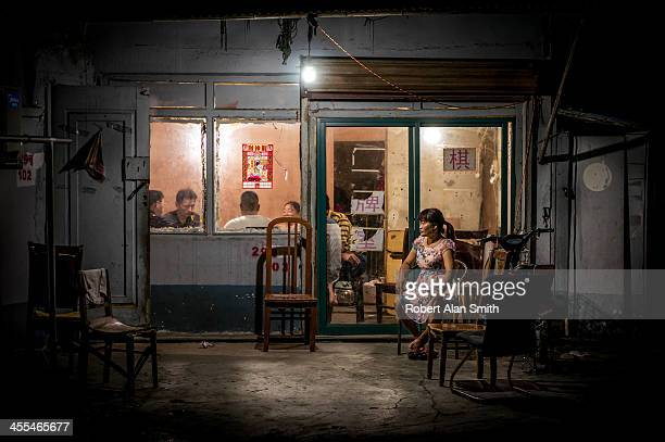 CONTENT] night shot of a small group playing MahJong in a small dimly lit room with one person sitting outside resting