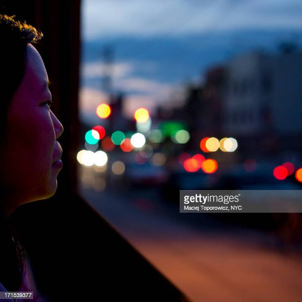 Night shot of a woman with city lights behind.