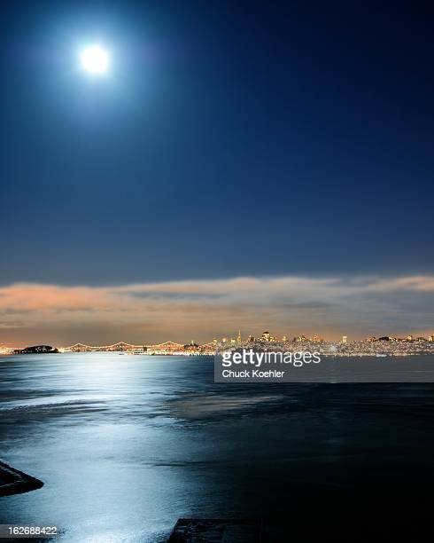 CONTENT] Night shot of San Francisco and the Bay Bridge from across the Moonlit Bay Beautiful reflections and colorful clouds illuminated by city...