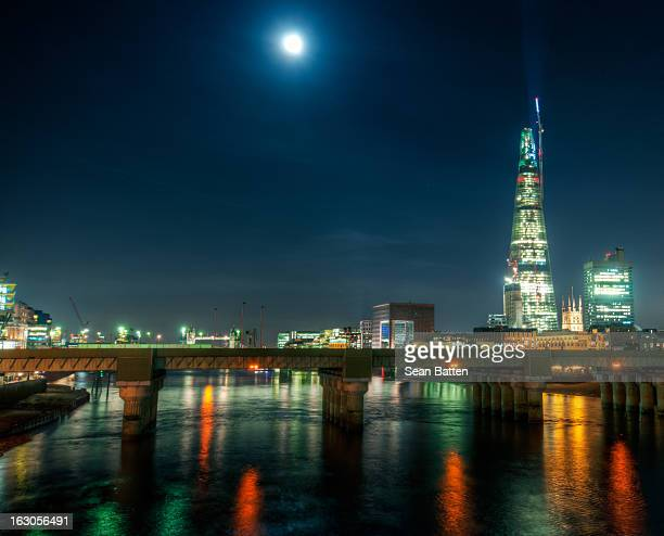 Night shot of The Shard from Southwark Bridge in London with the Thames reflectioning lights from a nearby bridge.