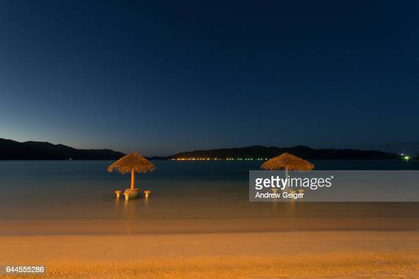 Night shot of two thatch covered tables along beach in ocean.