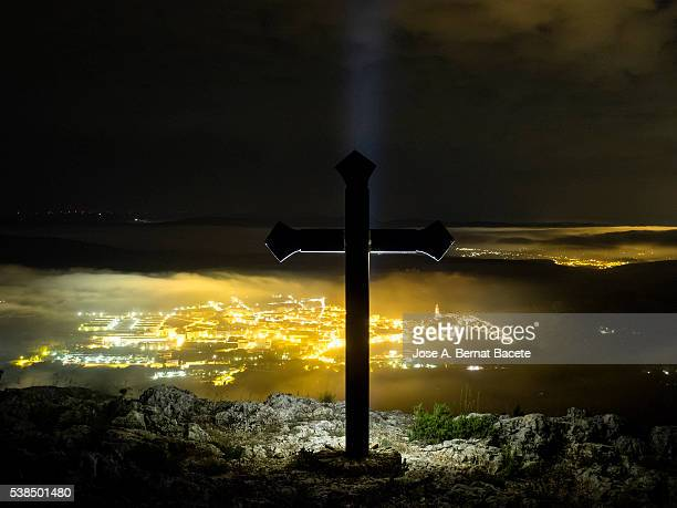 Night sight of the lights of a people with fog, from the top of a mountain with a great cross of iron.