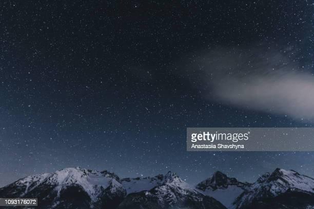 sternenklaren nachthimmel und schweizer alpen - nacht stock-fotos und bilder