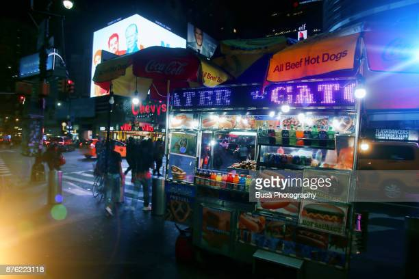 Night street scene in Midtown Manhattan: hot dog food cart along 8th Avenue. New York City, USA