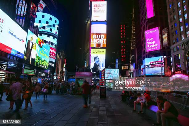 Night street scene in Midtown Manhattan: pedestrian plaza in Times Square, with One Times Square Building in the background. New York City, USA