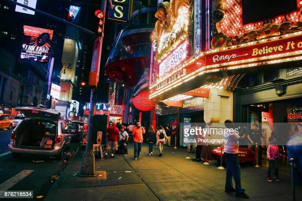 Night street scene in Midtown Manhattan: people under marquee of Ripley's Believe It Or Not along 42nd Street. New York City, USA