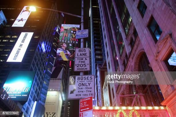 Night street scene in Midtown Manhattan: view from below of bus lane signs. New York City, USA