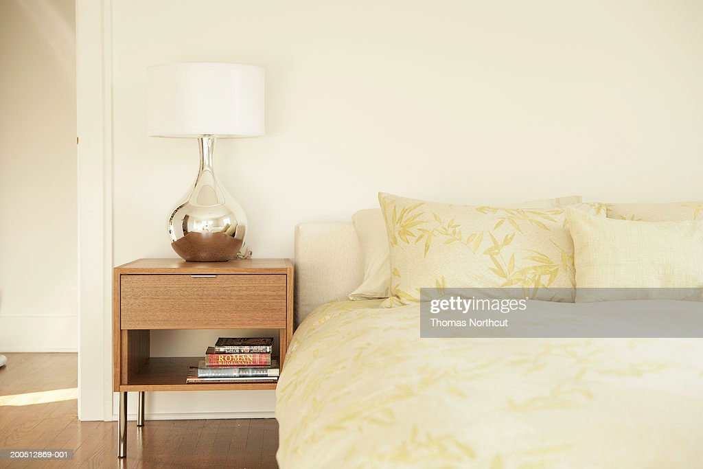 Night table and lamp beside bed : Stock Photo