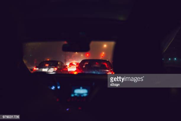 night time busy street view with illuminated car lights seen through car windshield at traffic jam - car interior stock pictures, royalty-free photos & images