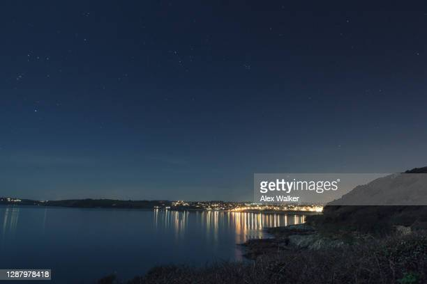 night time coastal scene of distant village illuminated at night - road stock pictures, royalty-free photos & images